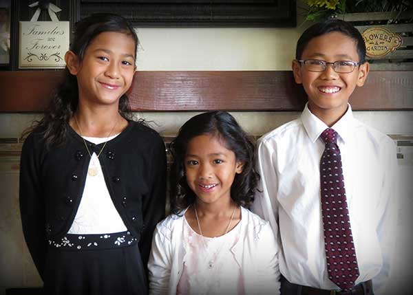 Three siblings smile in front of plaque that reads