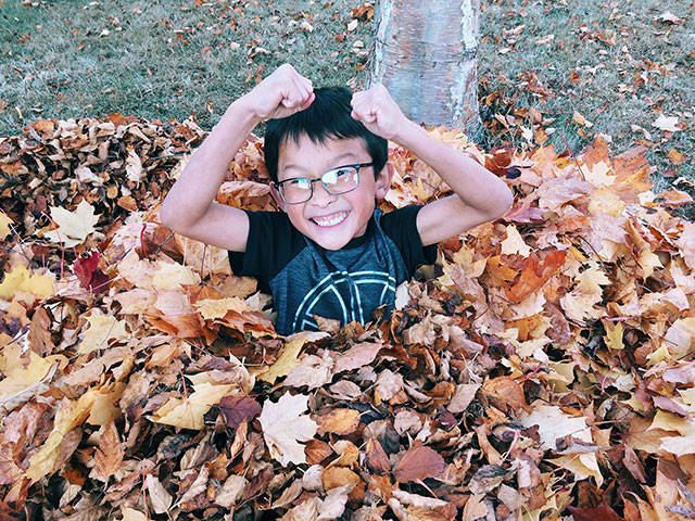 Elated child playing in a pile of fallen leaves
